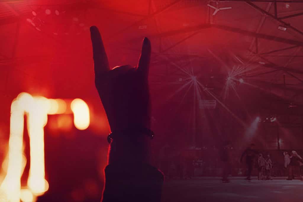 Hand mit ausgestreckten Zeige- und kleinen Finger vor eislaufenden Menschen im Eisstadion